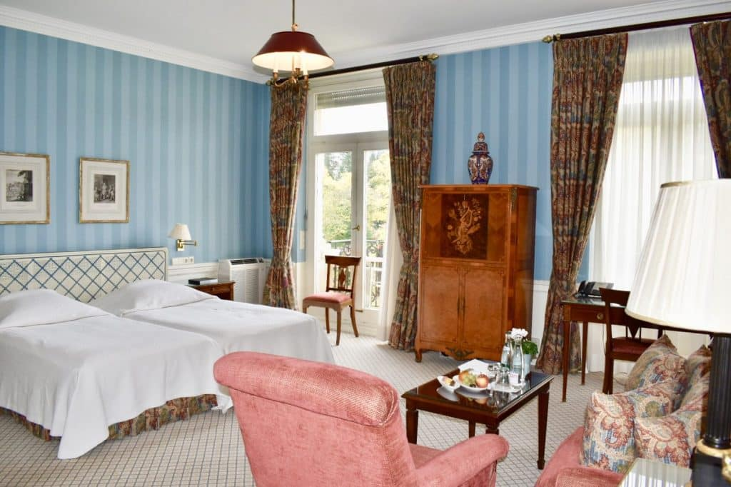 Beautifully decorated Brenners Park-Hotel & Spa suite; bed, desk, chairs and couch with two windows to balcony
