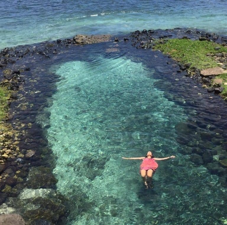 Alex in Samoa laying in the water