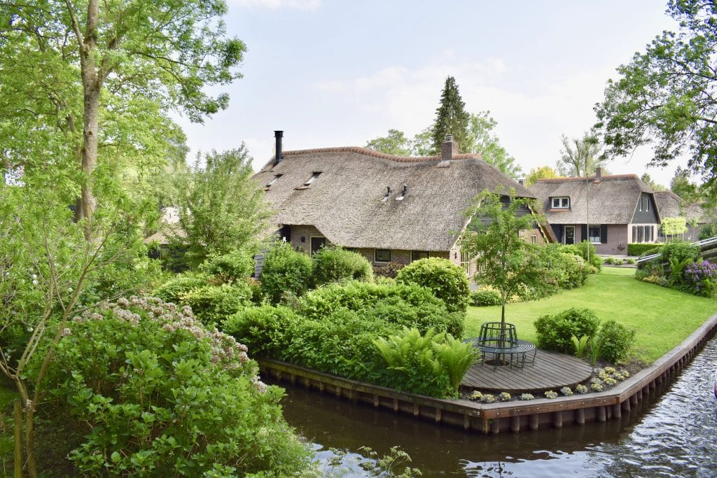 Picture from bridge of two homes with thatched roofs in Giethoorn on the waterway