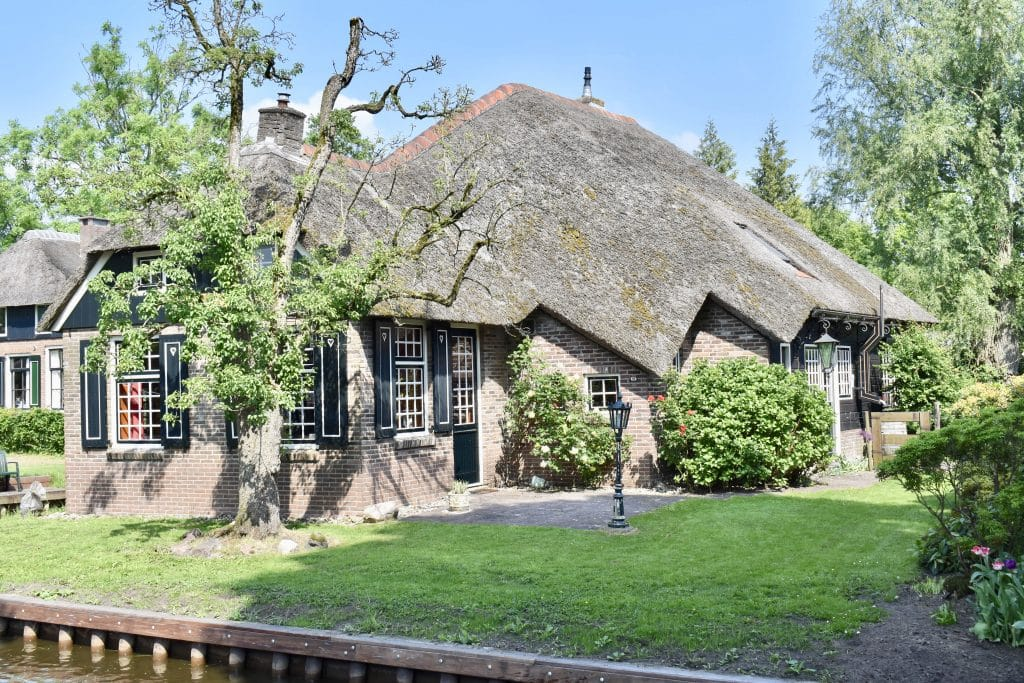 Thatched roof home with black shutters in Giethoorn Netherlands