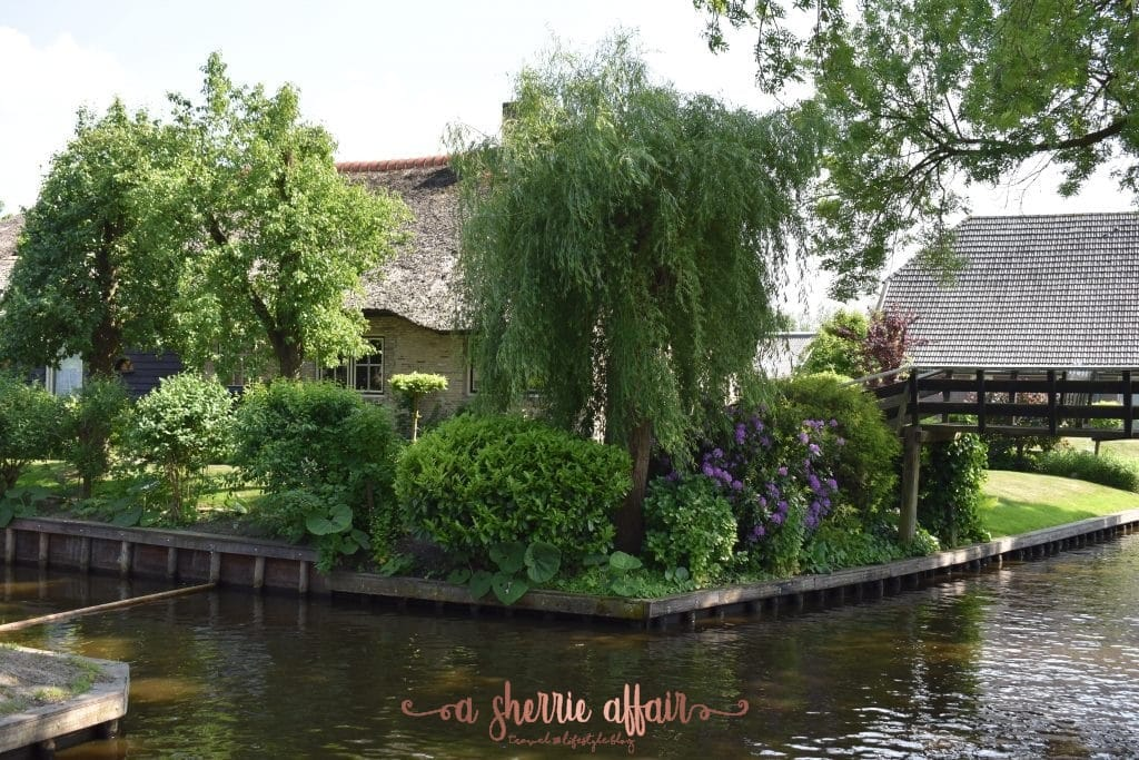 Turn in the canals in Giethoorn Netherlands with thatched roof home