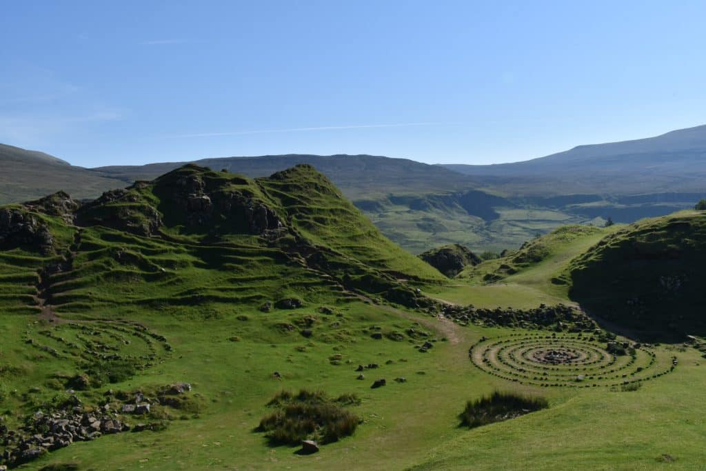 green lush hills looking over stone structures of the fairy glen